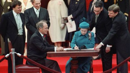 The image depicts Queen Elizabeth II who is signing Canada's constitutional proclamation in Ottawa on April 17, 1982, as Prime Minister Pierre Trudeau and other ministers look on.