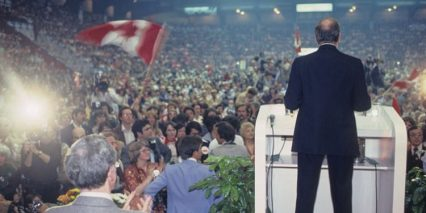 The photo depicts a back of the former Prime Minister Pierre Elliott Trudeau delivering a speech to a huge crowd of people during the 1980 referendum.