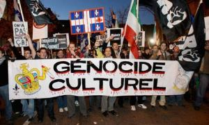 """The photo depicts francophone Quebecers protesting against the cultural genocide of their nation by English-Canadians. The protesters in the front of the photo are depicted holding a huge sign that reads """"Génocide Culturel"""", while protesters at the back are holding various other signs, including the flag of Quebec which has red paint dripping down, most likely symbolizing blood."""