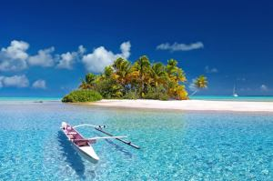 A canoe wades off the shore of a small island in turquoise blue water.