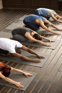 Cours de yoga en groupe - Une photo montrant un groupe de personnes qui fait du Yoga