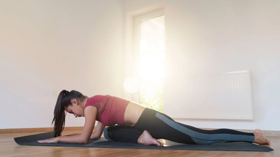 A woman rests in pigeon pose