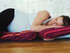 Gravid kvinna ligger på kuddar