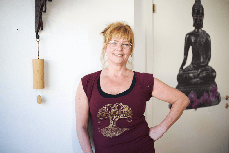 Blond yogalärare med glasögon står mot vit bakgrund
