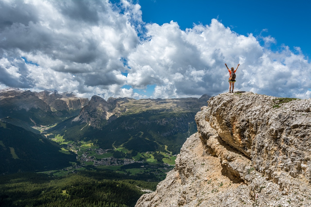 A person who has just climbed a mountain is standing at the very top and raises their arms triumphantly to the sky.