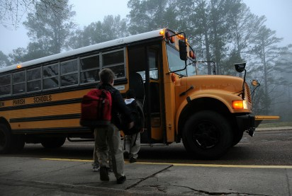 Kids climb onto a school bus.