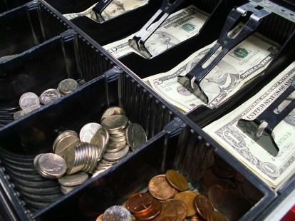 Coins and bills sitting inside a cash register
