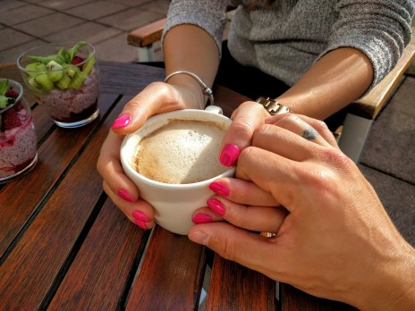 mother and daughter hold hands over coffee together