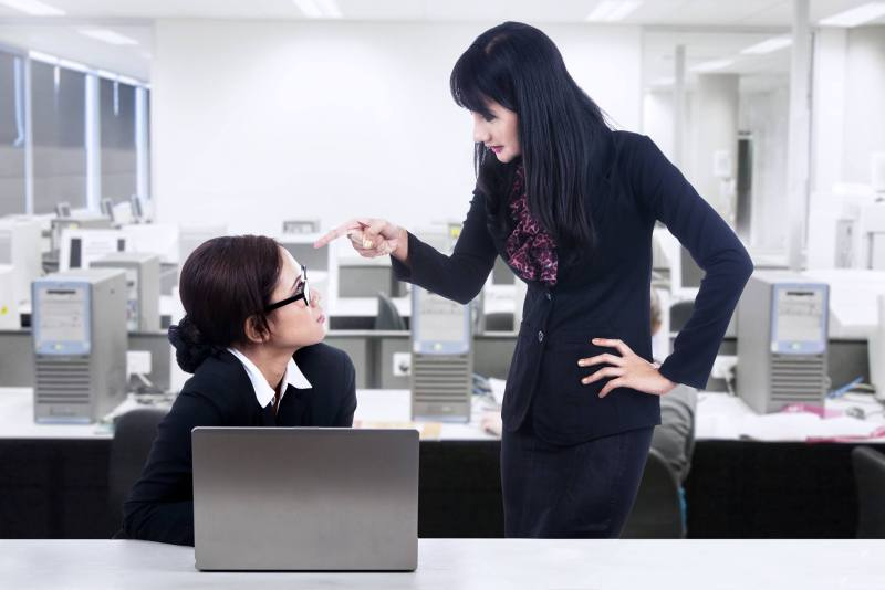 An employer stands over her employee, pointing a finger, and scolding as the employee looks up at her, frightened.
