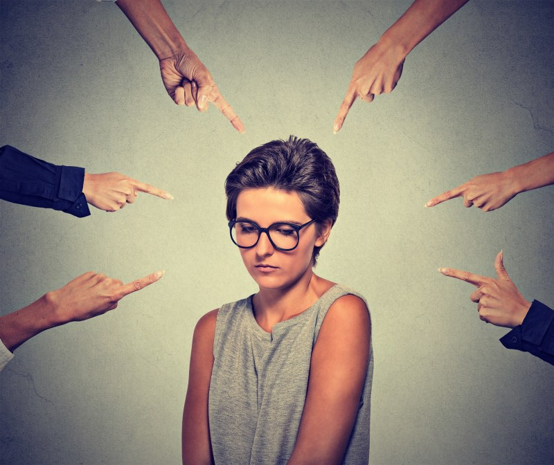 A sad looking person wearing glasses is surrounded by fingers pointing at her in shame