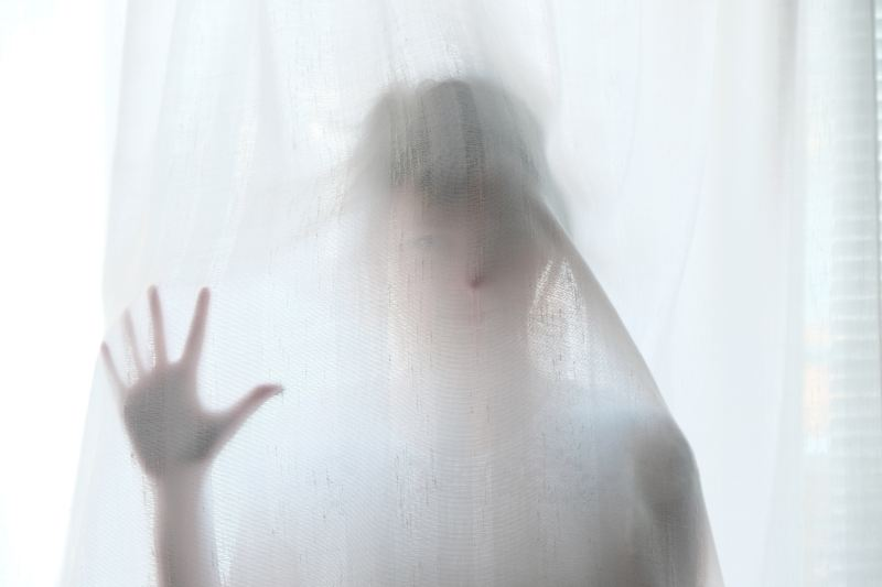 A person standing behind white sheets is almost invisible in a ghostly way.