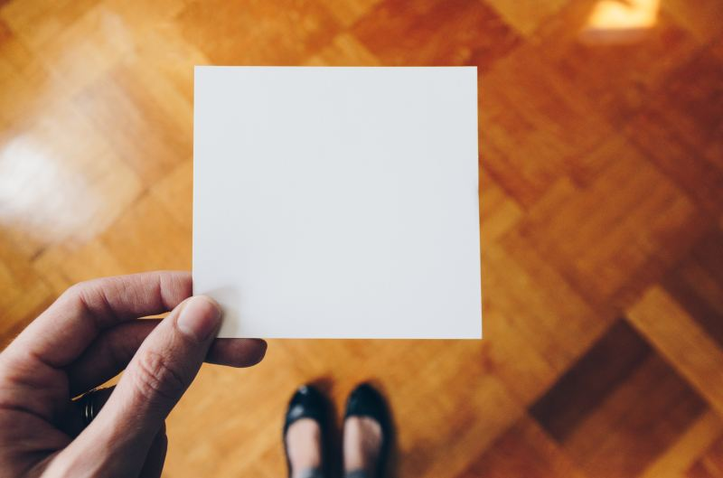 Someone holds a blank piece of paper, determining what to put on it
