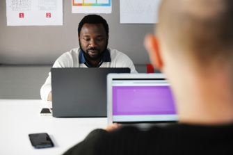 A black man and a white man work on their laptops, facing each other