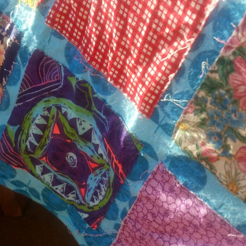 A cheerful portion of the quilt: shades of purple, turquoise, green, pink, and red, with a blue trim, lit in the sunlight.