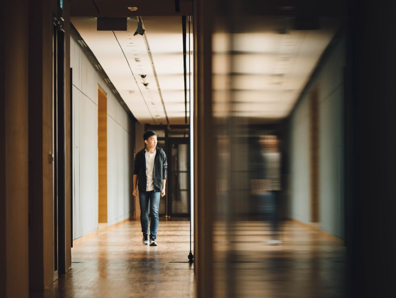 A teenage boy walks down a school hallway, while his distorted reflection walks beside him.