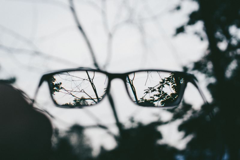 Looking through a pair of glasses, the world is transformed from blurry and dull to clear and crisp.