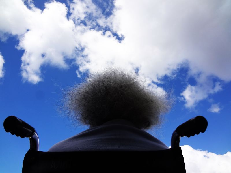 A person with big hair sitting in a wheel chair looks up at a very large blue sky.