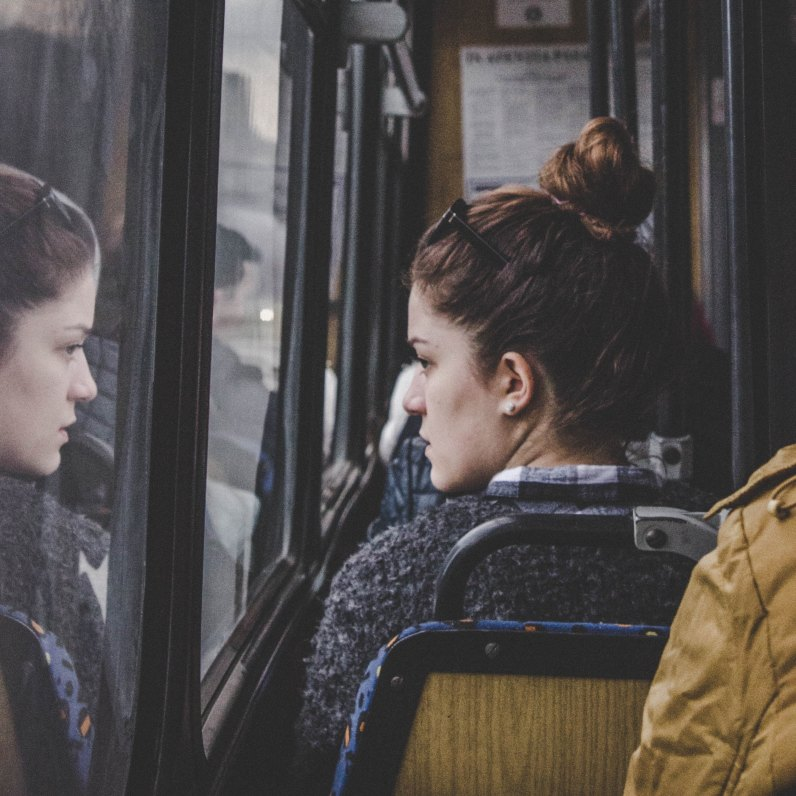 A woman stares into her own reflection in a bus window.