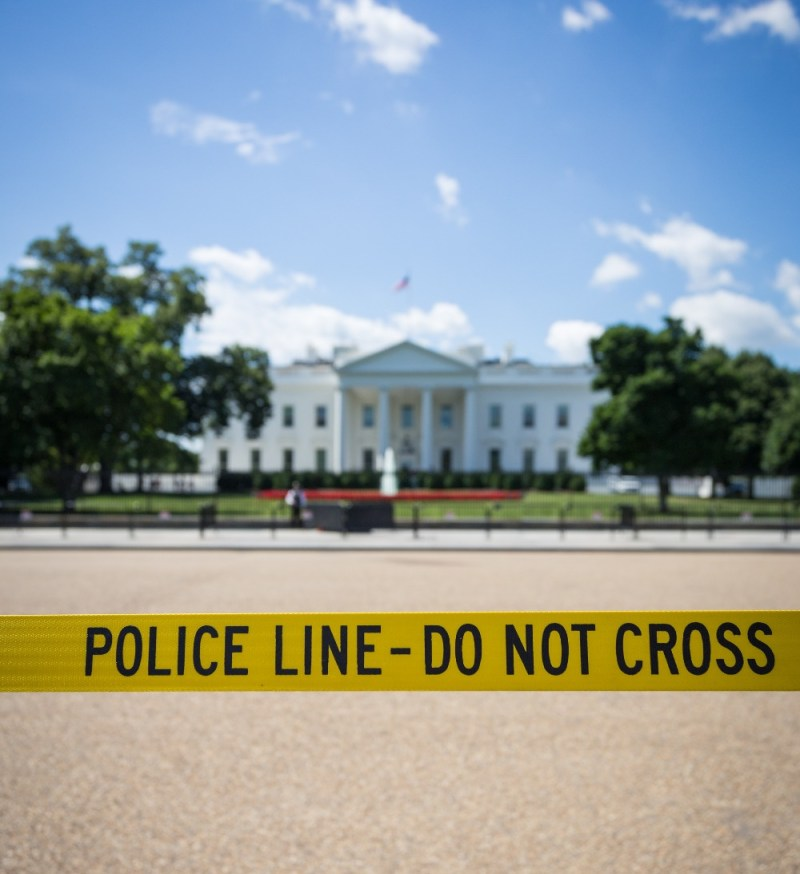 The path to the white house is blocked by a line of yellow police tape.