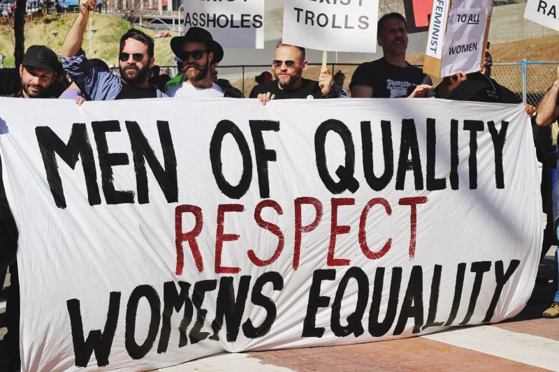 """A line of men at a protest hold a banner that says, """"Men of Quality Respect Women's Equality"""""""