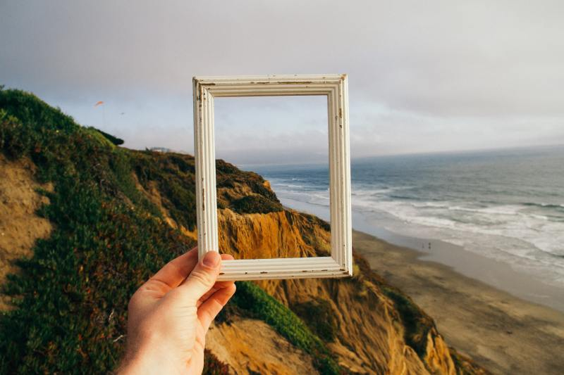 A light-skinned hand holds an old white picture frame with no backing up to capture a piece of the landscape in front of them in the frame: Sandy cliffs with small amounts of foliage and a blue ocean next to the beach.