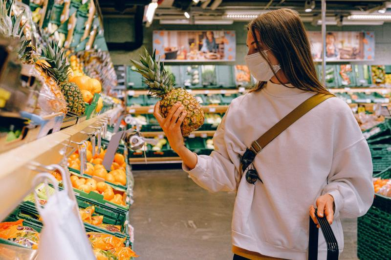 A light skinned woman with long light brown hair and a white sweatshirt wears a face mask and holds a pineapple, looking at it closely. She is standing in the produce section of a large grocery store.