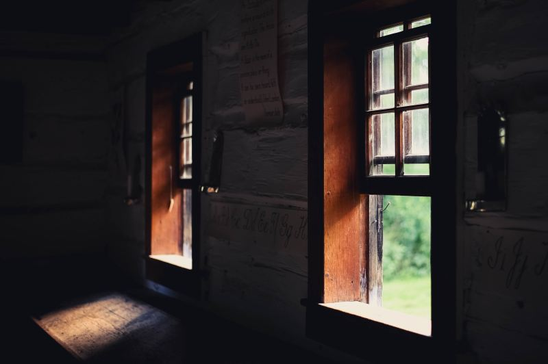 Two windows have been opened and bright sunny light shines through them into a dark room.