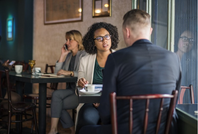 A white man and a black woman with natural hair sit at a table together at a cafe, plates and cups in front of them. The woman's face looks as if she's stunned, deeply angry, and considering how to express herself while the man looks casual as if nothing unusual has happened.