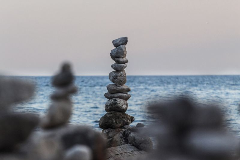 A collection of gray rocks stacked  in several columns, as one might do in as a form of meditation, with the blue ocean in the background.