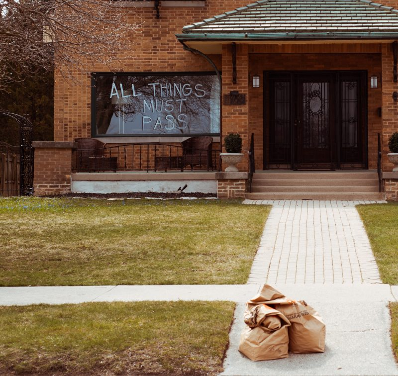 "In front of a brown brick house with a turquoise roof, large black metal door, a white walkway, and squares of green grass, there are several delivery bags sitting on the concrete and a large window in the front of the house that says in large letters ""All Things Must Pass."""