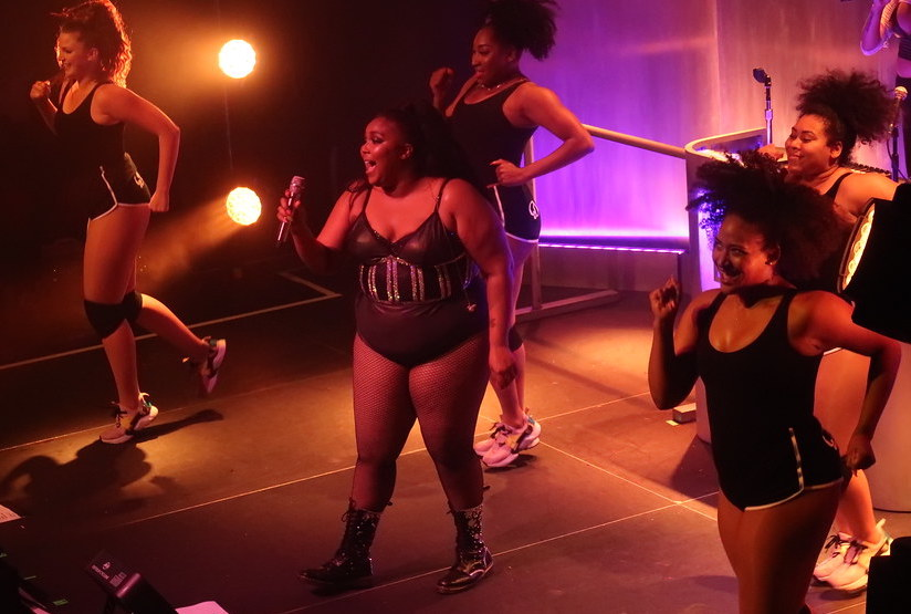 Lizzo, a large black woman in a black leotard with sparkly stripes, is center stage singing her heart out, surrounded by four other black women in black active wear actively dancing to her music.