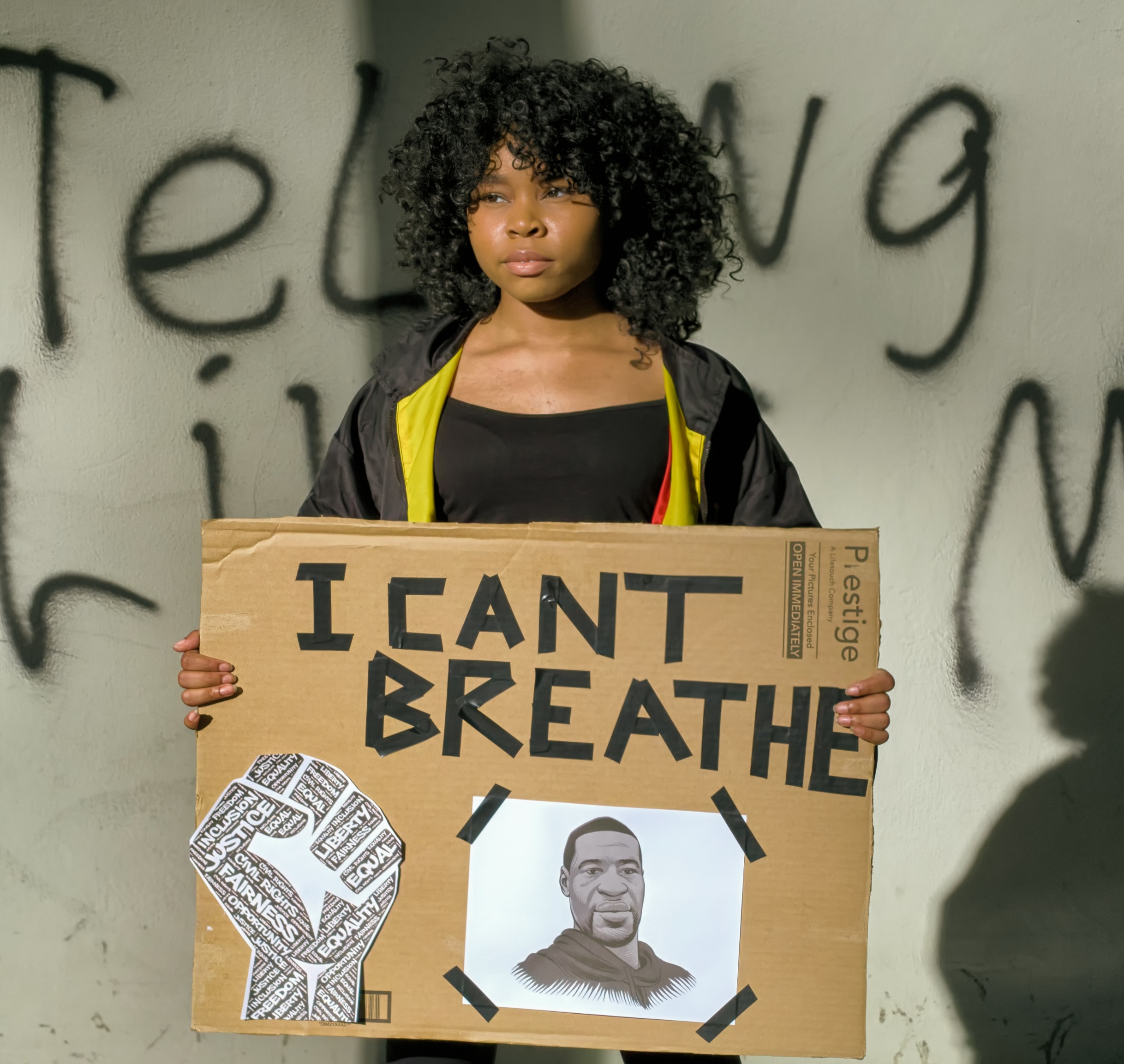 "A young black woman with loose curl natural black hair down to her shoulders stands tall holding a protest sign. The protest sign has ""I can"