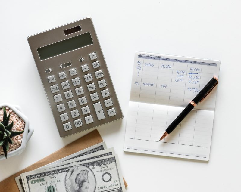 On a white background, there is a small calculator, a bank book filled with notations of costs and income, a nice black and gold pen, a succulent, and three fake 100- dollar bills.