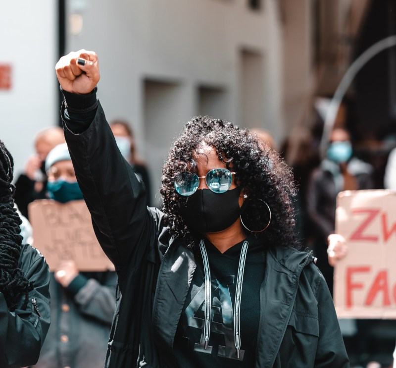 A woman with dark skin, shoulder length curly natural hair, and blue mirrored sunglasses, is dressed entirely in black including a black face mask. She holds her hand in a fist in the air. Other protesters holding signs surround her.
