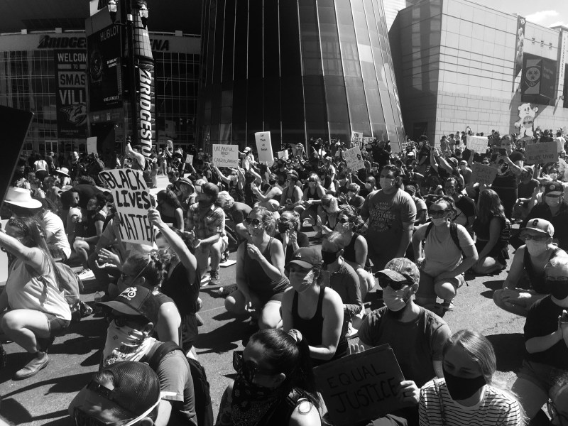Black and white photo of BLM protest in Nashville, TN. Dozens of people wearing masks sit down peacefully in the center of the street, holding their protest signs up, large buildings towering behind them.