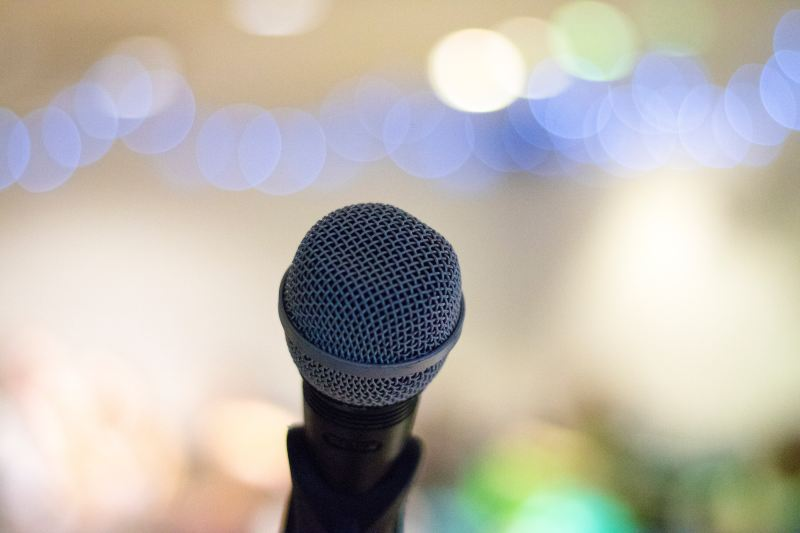 A hand microphone sits in its stand, an audience and event decorations in soft focus behind it. You cannot see the speaker so it could be anyone using the mic.