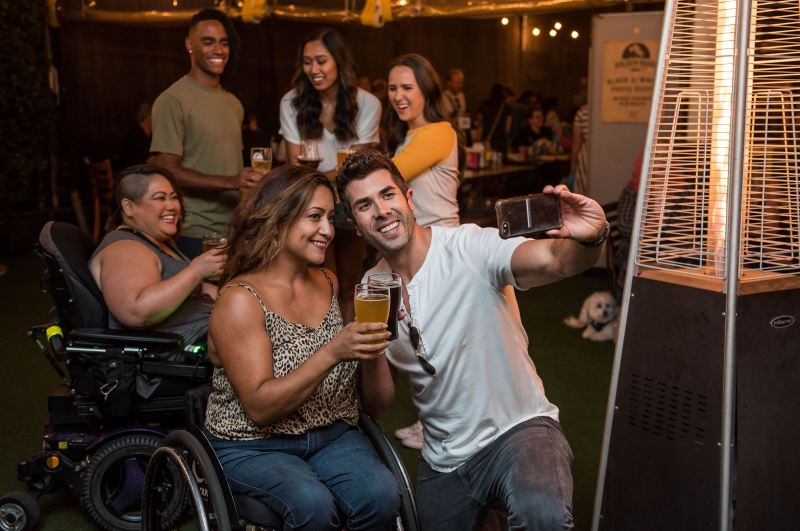 A group of friends hang out and take selfies at a bar while drinking beer. They have a variety of skintones and forms of disability, both visible and invisible.