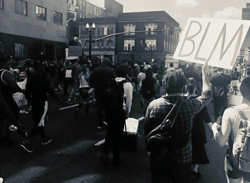 "Black and white photo of BLM protest in Nashville, TN. A large crowd walks through the street, mostly dressed in black. A nearby protestor holds a large sign that says ""BLM"" in all caps."
