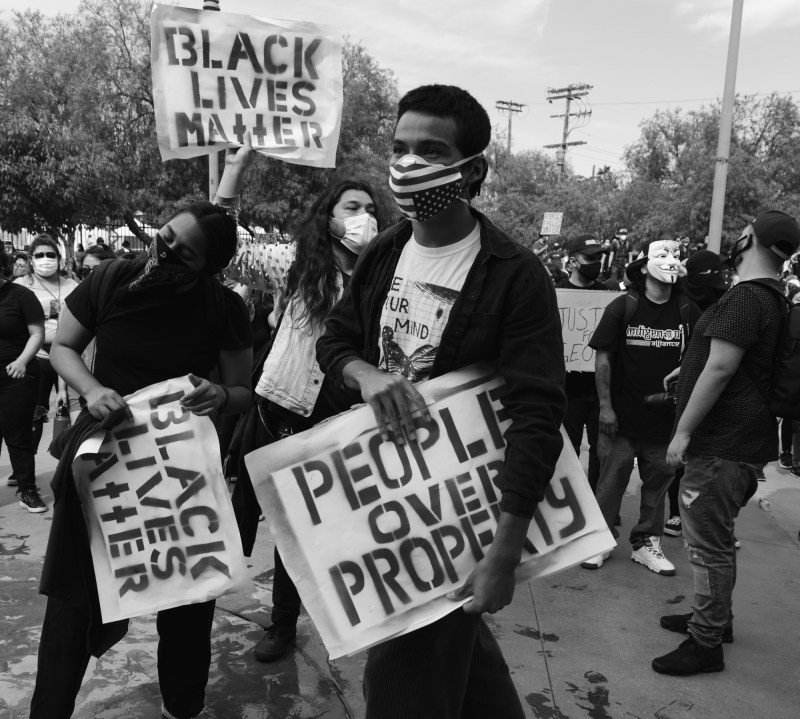 "A black man at a BLM protests wearing a mask with an upside down US flag, a white t-shirt, and a black jacket, holds a sign that says in big blocky letters ""People Over Property"". There are many protestors wearing masks and holding signs behind him."