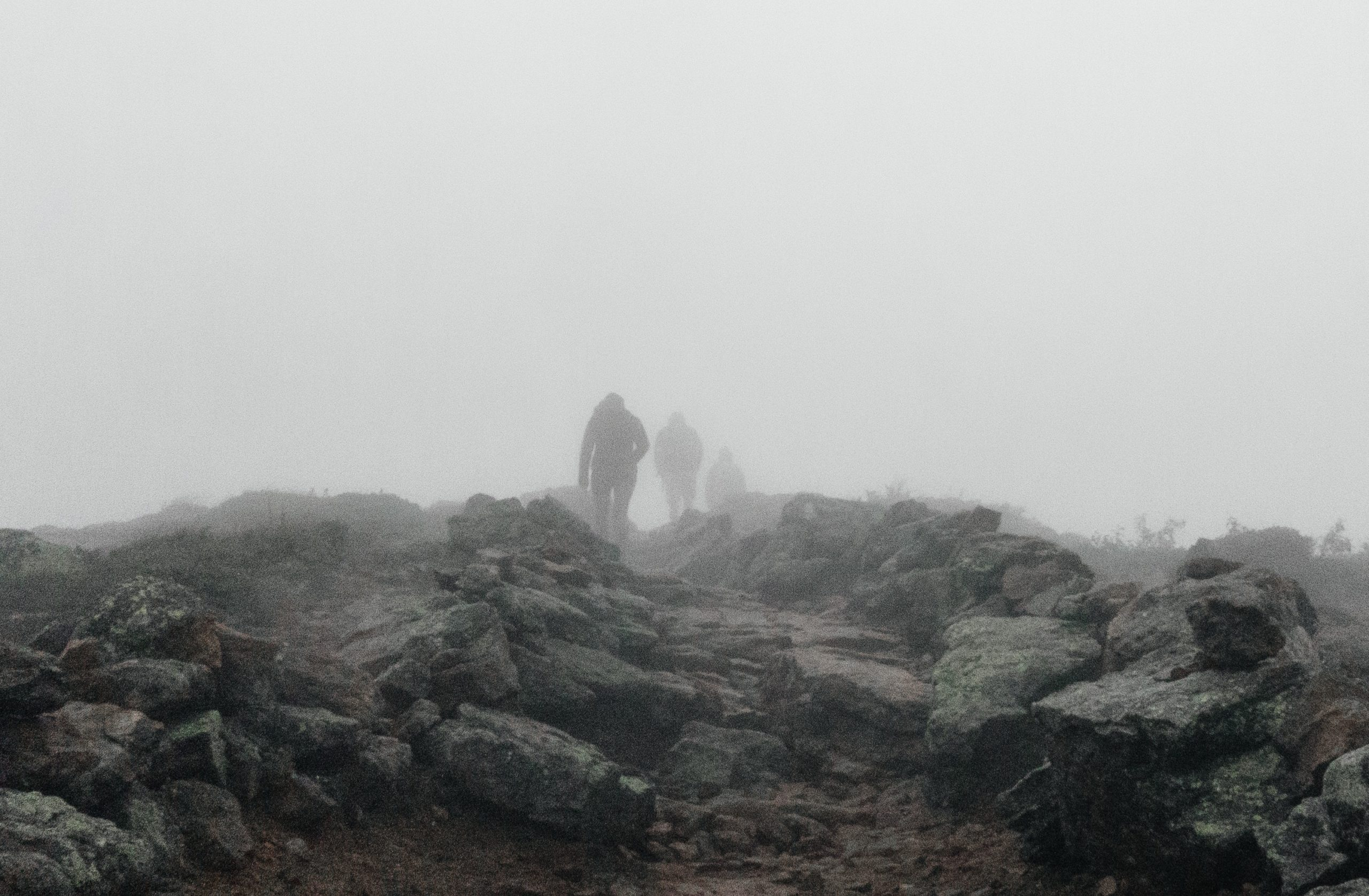 Several figured in the distance walk along path that is almost completely covered by large rocks. The sky is so thickly foggy that the figure who is the farthest away is almost obscured entirely. They look like they have a long journey ahead of them.
