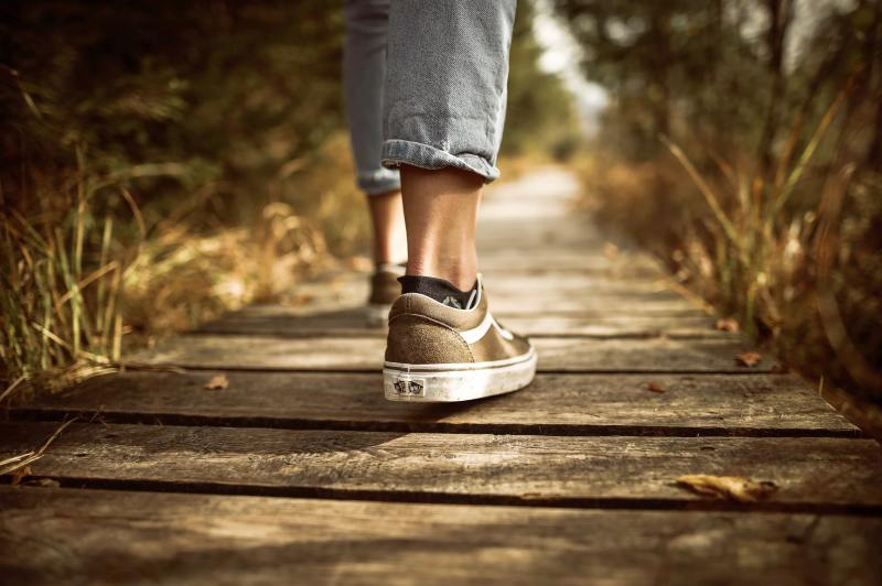 A person wearing faded jeans and sneakers takes their next step on the pathway stretching before them.