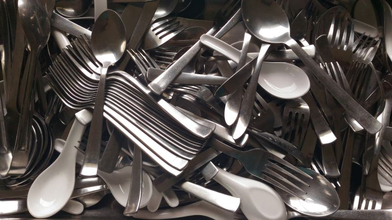 A drawer is filled with a chaotic mix of forks and spoons of many kinds.