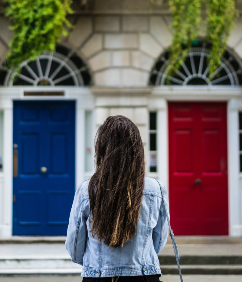 A woman stands in front of a pair of two doors that are identical except for one is red and one is blue, trying to make a decision about which door to go through.