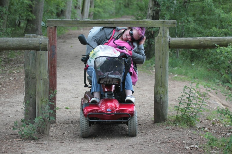 A woman riding a red motorized scooter has to duck down uncomfortably low to get under a wooden plank  blocking the dirt path unnecessarily.