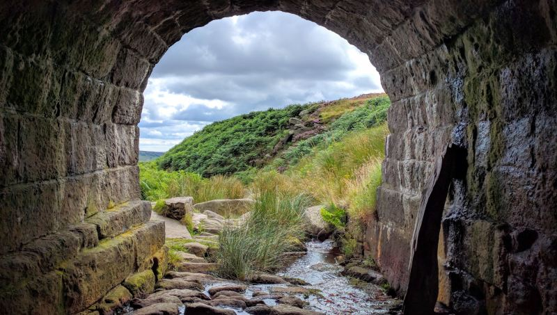 Come to the end of an old stone tunnel, you can see green bushes on the hill ahead and that the storm clouds are starting to clear away.