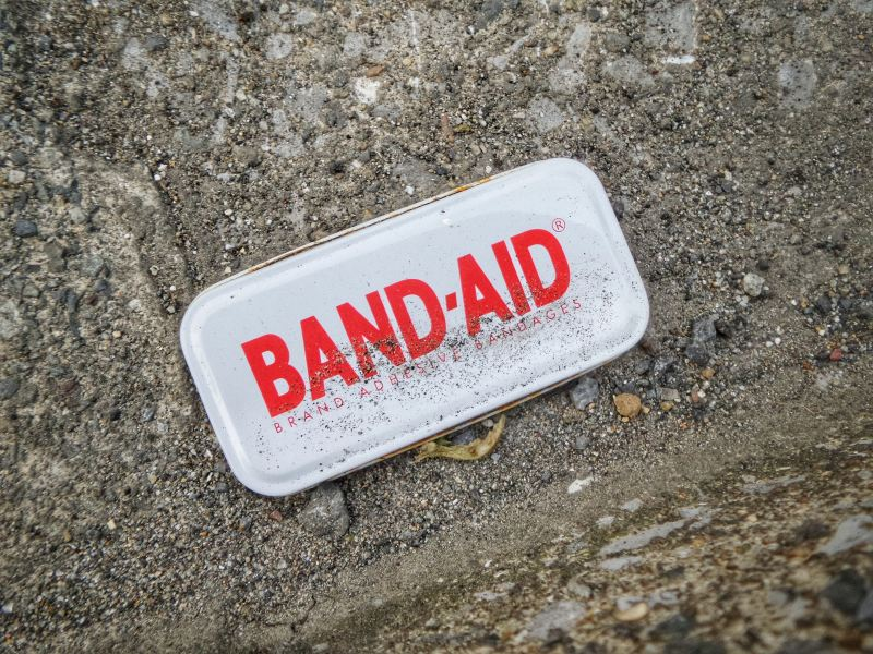 The top of a band-aid's tin sits in the dirt, surrounded by gravel.
