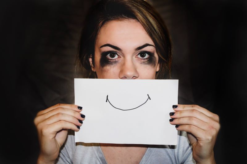 A woman with heavy black eye makeup has been crying so much her makeup is smeared all over her face, but she is holding a white piece of paper over her mouth with a smile drawn on it.