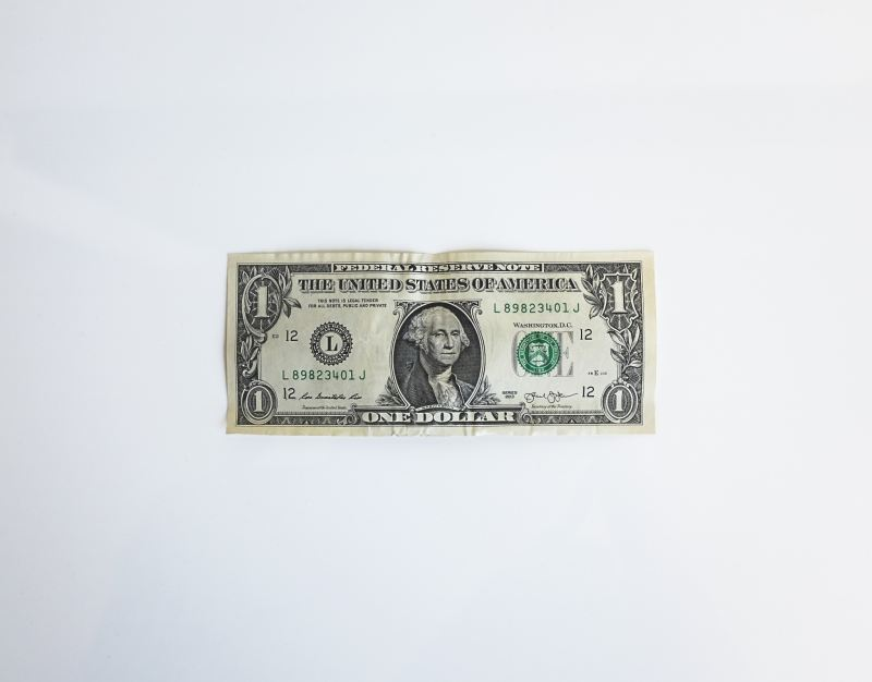 A single dollar bill lying flat on a light grey to white gradient background.