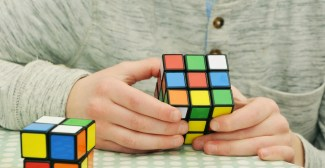 A person wearing a beige and grey patterned button up sweater holds an unsolved 3x3 rubik's cube in their hands, contemplating how to solve it. Another 2x2 rubik's cube sits next to them on the table.