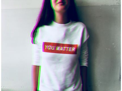 "A person is wearing a white shirt, only their torso and the bottom half of their face is visible. On the shirt is a red rectangle with white text that says, ""YOU MATTER."""